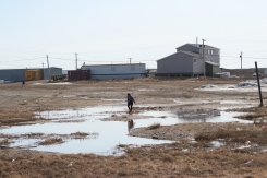 A child plays in some puddles outside of Tuktoyaktuk's Mangilaluk School. Tuktoyaktuk, N.W.T. May 2019