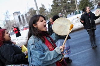 An Indigenous youth passionately beats her drum during a demonstration that was organized by Wet'suwet'en supporters outside of the Justice Building in Ottawa, Ont. on Feb.12, 2020.