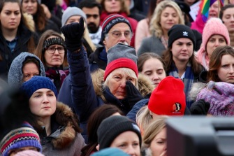 A woman wipes her eye as she raises a fist in the air during the second annual Women's March in Ottawa on Jan. 20, 2018.