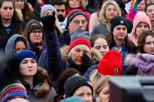 A woman wipes her eye and raises a fist in the air during the second annual Women's March in Ottawa on Jan. 20, 2018. Shot for Centretown News