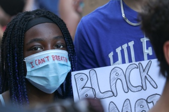 """A Black woman wears a surgical mask with """"I CAN'T BREATHE"""" written on it at a George Floyd solidarity march outside of the US Embassy on Sussex Drive in Ottawa, Canada on June 5, 2020. After meeting at Parliament Hill, tens of thousands peacefully marched through various streets in the downtown area. """"I can't breathe"""" were the final words uttered by George Floyd and Eric Garner, two African American men who were killed in separate incidents of police brutality in the United States."""