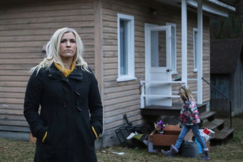 Amy Makortoff stands outside of her new home in Nelson, B.C., while her eight-year-old daughter Elvie roams the yard. December 2020. Shot for The Globe and Mail