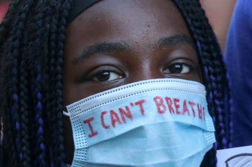 """A young woman wearing a surgical mask with """"I can't breathe"""" written on it marches in a Black Lives Matter rally in Ottawa on June 5, 2020. Tens of thousands took to the streets of downtown Ottawa to protest police brutality and anti-Black racism."""