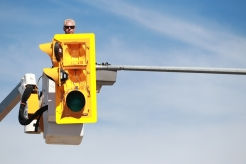 A Westcana Electric employee installs a new yellow traffic light box in Creston, B.C. on Sept. 4, 2020.