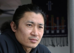 """Zaudanawng """"Jay-Dan"""" Maran looks outside his window at his Creston, B.C., home on Jan. 22, 2021. In 2007, Maran was forced to flee his home in the Kachin State of Myanmar after he helped a woman escape the hands of two soldiers who were sexually assaulting her. He came to Creston in 2014, after hiding out in Malaysia for several years, waiting to receive his refugee card status. Hanging on the wall behind him is a logo of Kachin's Manaw festival. Shot for the Creston Valley Advance"""
