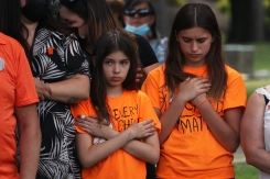 Two youth cross their arms during a memorial event in Kelowna in honour of the 215 Indigenous children whose remains were discovered at the site of the former Kamloops Indian Residential School. June 2021