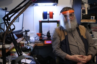 Richard Murray sits in his office as his 3D printer works on a face shield in the background. December 2020. Creston, B.C.